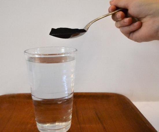Ложка активированного угля и вода